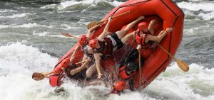 Whitewater rafting raft flips over on the Nile River. Go on safari with Kwezi Outdoors